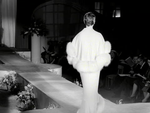 model walks down a catwalk wearing a reversible fur trimmed cape and evening gown at a fashion show. 1954. - fashion show stock-videos und b-roll-filmmaterial