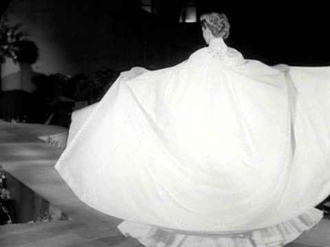 a model walks down a catwalk wearing a white ball gown with a full length cape at a fashion show 1954 - cape stock videos & royalty-free footage