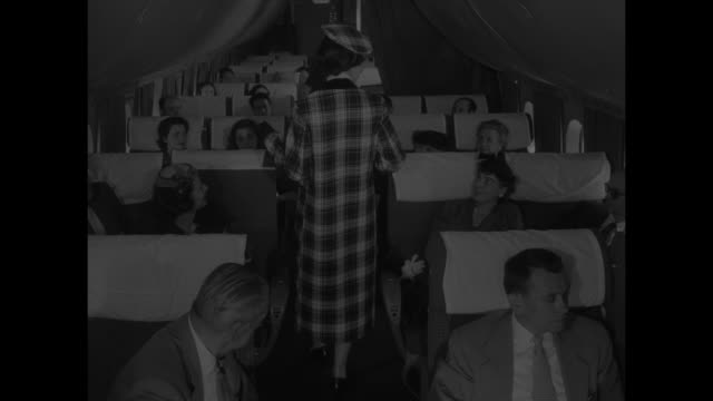 vs model walks down aisle of airplane towards camera displaying plaid coat and hat she has on passengers in seats / model comes down steps into... - plaid stock videos and b-roll footage