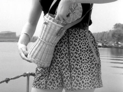 vídeos y material grabado en eventos de stock de model wearing a blouse and shorts takes out a pair of sunglasses from a wicker handbag and puts them on whilst standing on the deck of a boat on the... - bolso