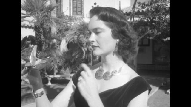 model wearing a floor-length gown and silver jewelry checks her lipstick in a silver compact while standing in a spanish-style courtyard of the royal... - gårdsplan bildbanksvideor och videomaterial från bakom kulisserna