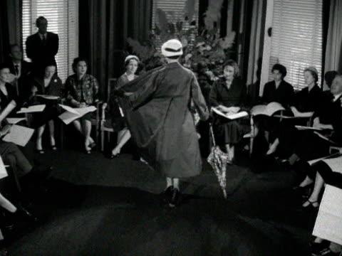 vídeos y material grabado en eventos de stock de model wearing a floral dress with a coat and hat curtseys in front of queen soraya at a private fashion show. 1955. - colección de la moda