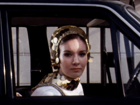 a model wearing a hat covered in large gold sequins looks out of a car window 1969 - hat stock videos & royalty-free footage