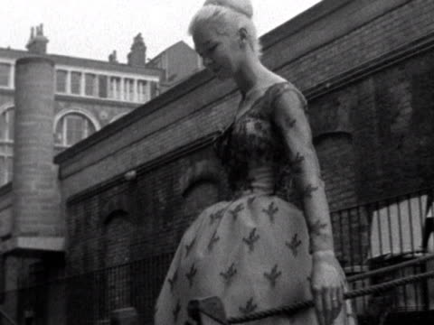 model wearing a lace cocktail gown walks down a gangplank and onto a barge next to the mermaid theatre. 1960. - lace textile stock videos & royalty-free footage