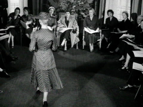 stockvideo's en b-roll-footage met a model wearing a polka dot hat coat and dress parades in front of an audience including queen soraya of persia 1955 - stippen