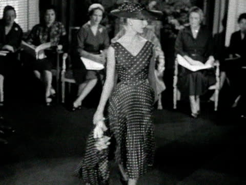stockvideo's en b-roll-footage met a model wearing a polka dot hat coat and dress twirls for the audience at a private fashion show 1955 - stippen