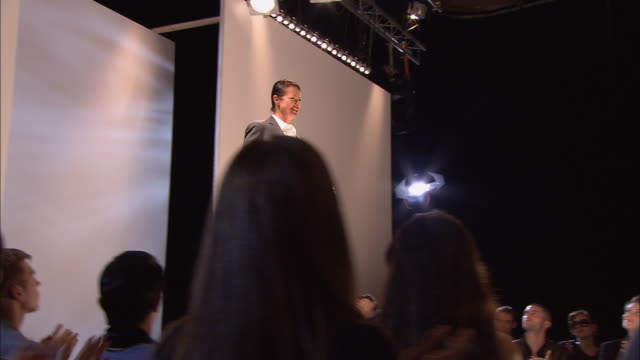 MS TU Model wearing a suit with a large belt around the waist standing and posing on catwalk in front of audience at fashion show/ London, England