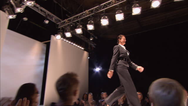 vídeos de stock, filmes e b-roll de ms pan model wearing a suit with a large belt around the waist walking and posing on catwalk in front of audience at fashion show/ london, england - desfile de moda