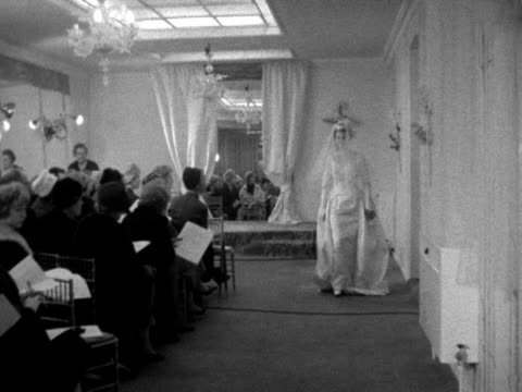 a model wearing a wedding dress turns and walks towards the camera at a fashion show 1961 - 頭飾り点の映像素材/bロール