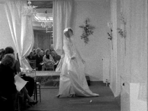 vídeos y material grabado en eventos de stock de model wearing a wedding dress turns and walks towards the camera at a fashion show. 1961. - vestimenta para mujer