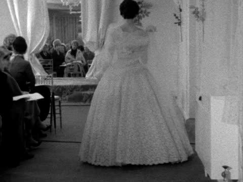 vídeos de stock, filmes e b-roll de a model wearing a wedding dress walks towards the camera at a fashion show 1961 - papel em casamento