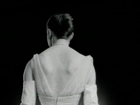 stockvideo's en b-roll-footage met a model wearing a white evening gown turns at a fashion show 1955 - jurk
