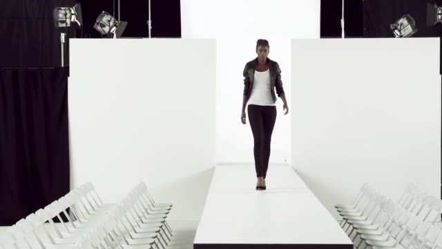 Model wearing black leather jacket on catwalk at fashion show
