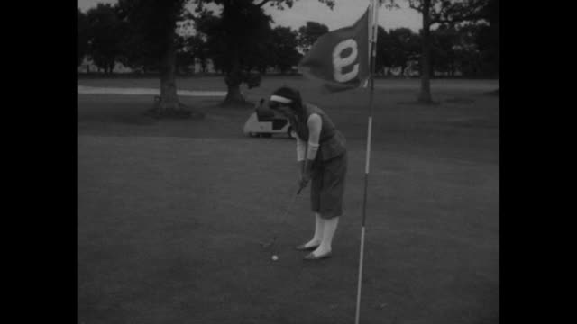 "model wearing ""plus fours"" and sleeveless belted jacket walks from golf cart to flagstick on green; vs she putts, overshoots and undershoots cup /... - sleeveless top stock videos & royalty-free footage"
