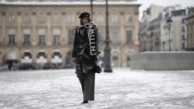 vídeos y material grabado en eventos de stock de model wears a beret, a black shiny pvc trench coat, a black and white scarf, a chanel bag, flare pants, outside alexis mabille, during paris fashion... - bufanda