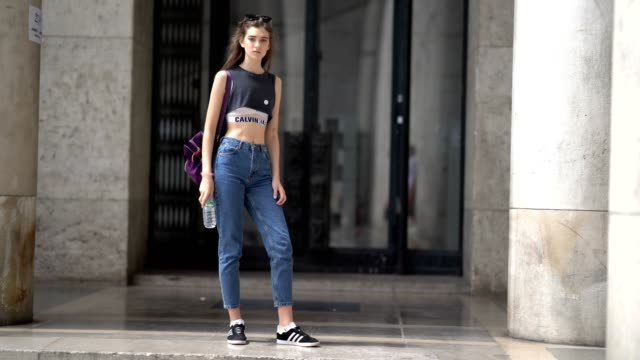 model wears a black bare belly sleeveless top, calvin klein bras, blue denim cropped jeans, a purple bag, sneakers shoes, outside the 22/4 hommes... - sleeveless top stock videos & royalty-free footage