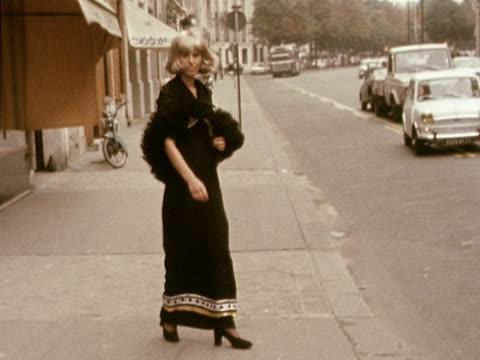 A model wears a black evening dress with a sequinned bra top and feathered cape designed by Torrente 1972
