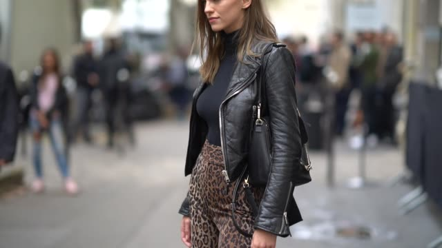 A model wears a black leather perfecto jacket leopard print pants black shoes outside Chloe during Paris Fashion Week Womenswear Spring/Summer 2018...