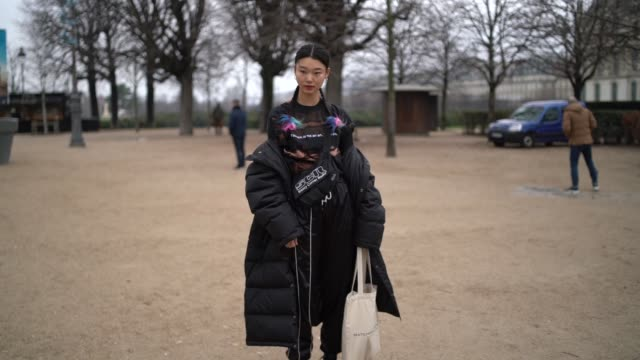 stockvideo's en b-roll-footage met a model wears a black top with multicolored pattern a black parka black pants black platform military boots a white tote bag a black fanny bag... - week