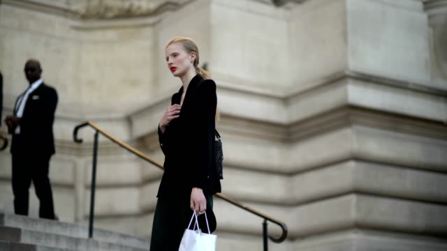 A model wears a blazer jacket green pants black leather shoes a black bag outside the Giambattista Valli show during Paris Fashion Week Haute Couture...