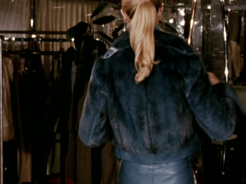 A model wears a blue fur jacket over blue leather dungarees designed by Ted Lipadus 1972