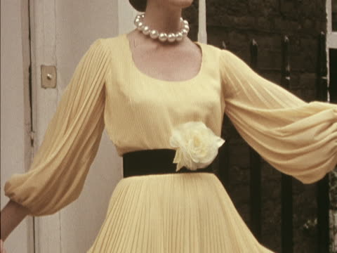 model wears a bright yellow muslin dress, designed by hardy amies. - dress stock videos & royalty-free footage