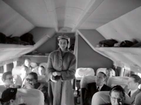a model wears a coat during an inflight fashion show onboard a passenger aircraft - flugpassagier stock-videos und b-roll-filmmaterial