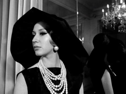 A model wears a cocktail dress and a large black hat designed by Norman Hartnell 1961