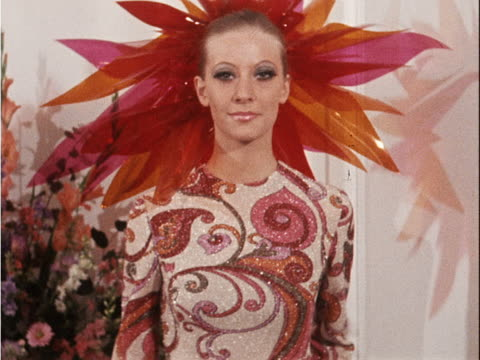 A model wears a floral patterned evening gown with an elaborate plastic hat core number ANB6546K