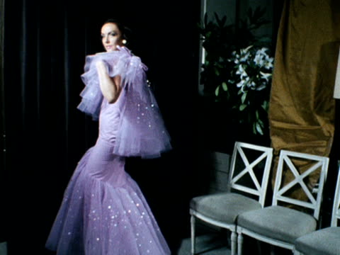 A model wears a frilled lilac coloured evening dress designed by Norman Hartnell 1968