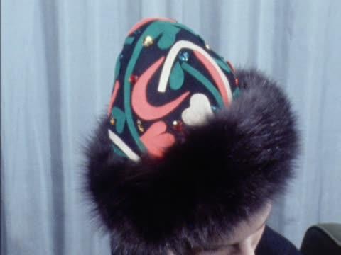 stockvideo's en b-roll-footage met a model wears a fur trimmed patterned hat - dameskleding