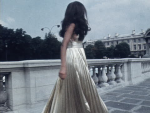 A model wears a gold lame evening gown