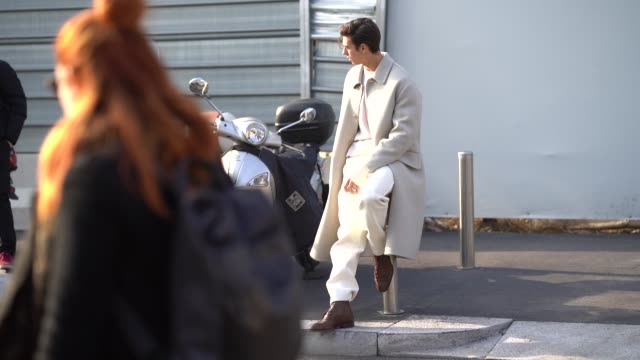 A model wears a gray trench coat white pants during Milan Menswear Fashion week Fall/Winter 2018/19 on January 14 2018 in Milan Italy