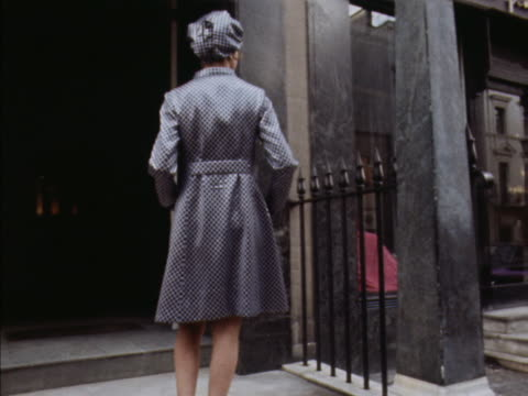 model wears a grey checked coat with matching hat, designed by norman hartnell. - デザイナー服点の映像素材/bロール