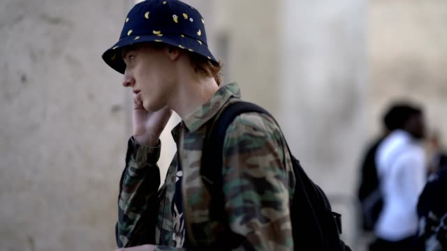 model wears a hat, a military camouflage print jacket, a flower print top, gray shorts, white socks, sandals, outside the 22/4 hommes show, during... - gray jacket stock videos & royalty-free footage