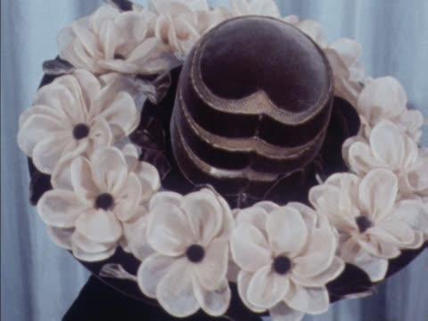 stockvideo's en b-roll-footage met a model wears a hat decorated with flowers - dameskleding