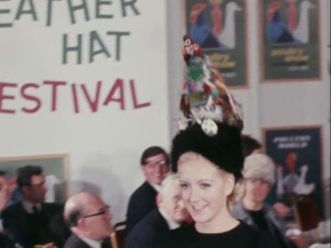 stockvideo's en b-roll-footage met a model wears a hat with a fake chicken on top at the feather hat festival in london - dameskleding
