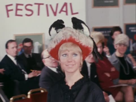 stockvideo's en b-roll-footage met a model wears a hat with two fake magpies on its top at the feather hat festival in london - dameskleding