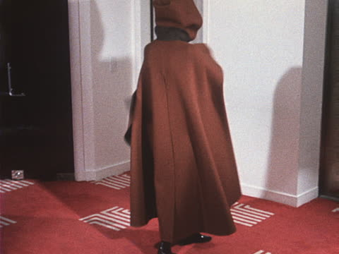 A model wears a hooded cape and matching dress