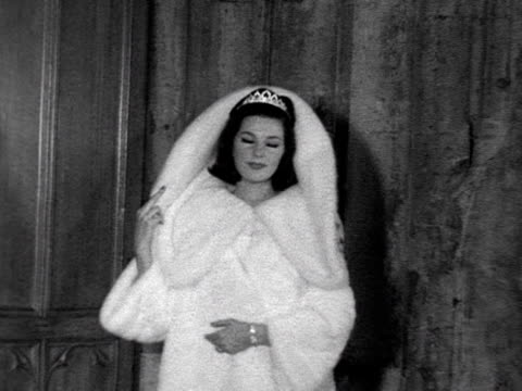model wears a hooded white mink coat at a fashion show at the guildhall. 1962. - rathaus stock-videos und b-roll-filmmaterial