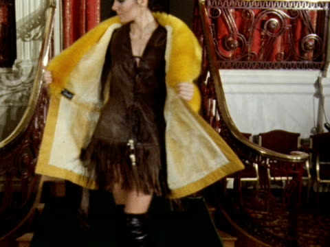 A model wears a leather tassled mini dress with a yellow fur coat