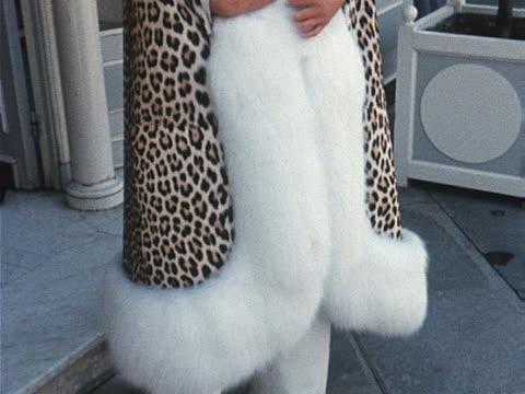 stockvideo's en b-roll-footage met a model wears a leopard print coat trimmed with white fox fur - kleding