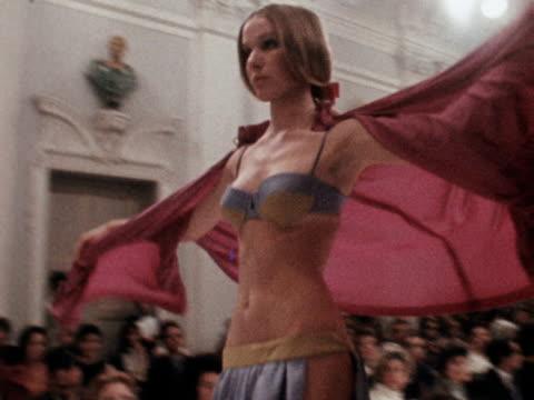 vídeos de stock, filmes e b-roll de model wears a lightweight pink cape over a bikini with envelope flaps along a runway at an emilio pucci fashion show. 1969. - lightweight