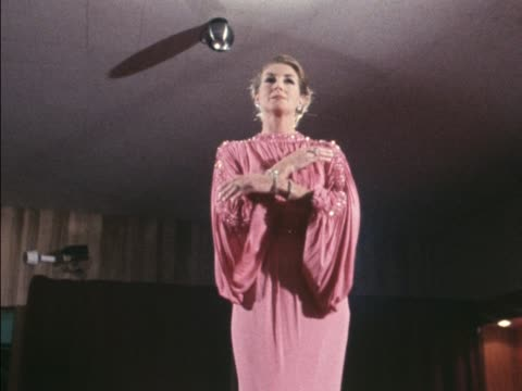 stockvideo's en b-roll-footage met a model wears a norman hartnell pink evening gown and a selection of precious jewellery - dameskleding