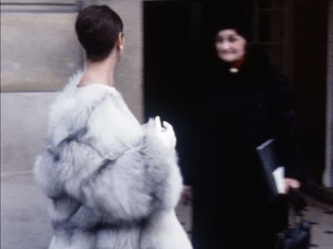 A model wears a Pierre Balmain fur coat and white cocktail dress