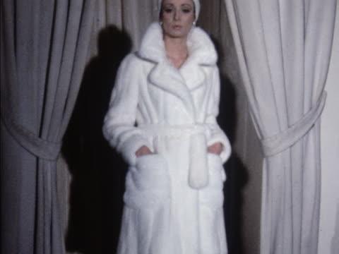 A model wears a Pierre Balmain white mink trench coat
