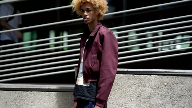 A model wears a purple jacket brown and blue pants and has dyed hair outside the Y3 show during Paris Fashion Week Menswear Spring/Summer 2018 on...