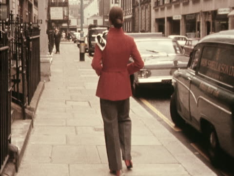 A model wears a red jacket and black trousers designed by Hardy Amies