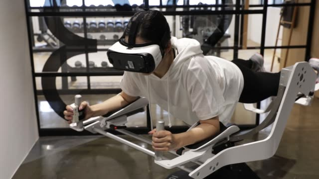 vidéos et rushes de a model wears a samsung electronics co gear virtual reality headset as she demonstrates using the icaros vr fitness machine manufactured by icaros... - casque téléphonique