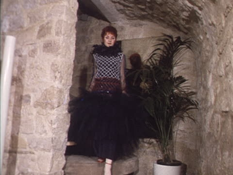 A model wears a sequinned evening gown and a feather boa